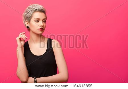 beautiful woman with short blond dyed hair and clean makeup looking to the side over pink color background with copy space