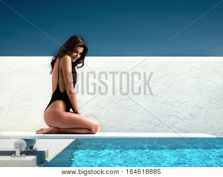 woman sitting on springboard at the pool
