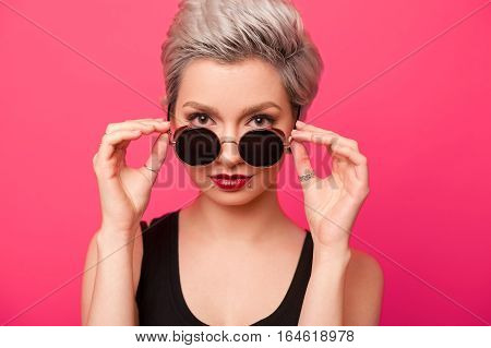 Young trendy woman with short dyed hair wearing Steampunk vintage retro sunglasses. Closeup portrait of girl with stylish round circle shades looking at camera over pink color background
