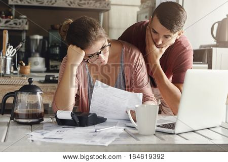 Young Stressed Caucasian Couple Facing Financials Troubles, Sitting At Kitchen Table With Papers, Ca