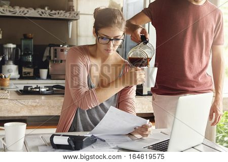 Beautiful Woman In Glasses Holding Piece Of Paper, Doing Paperwork And Paying Taxes At Kitchen Table