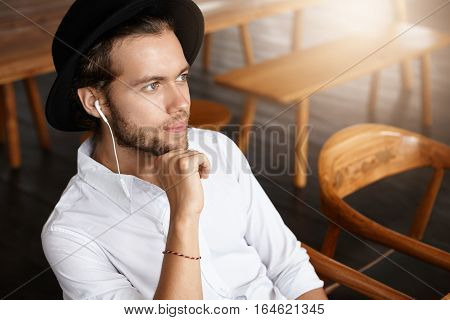 Fashionable Happy Young Man Wearing Black Hat And Earphones Daydreaming, Enjoying New Music Album Of