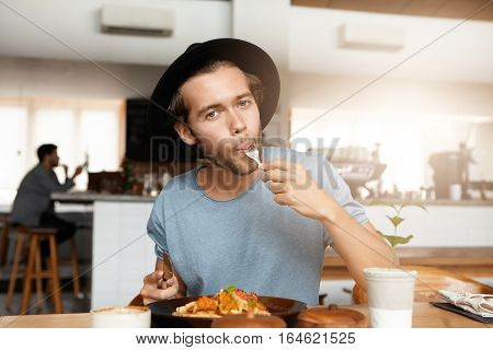 Fashionable Young Man Enjoying Tasty Food For Lunch Sitting At Wooden Table Of Cozy Restaurant. Hung