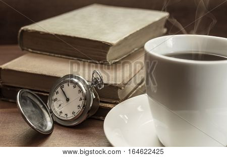 Still life with old pocket watch cup of coffee and old books on wooden table. Selective focus.