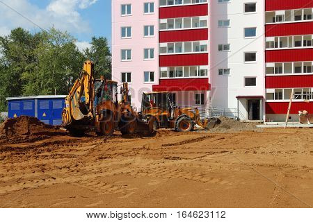 Two tractors work on sand on construction site at summer sunny day