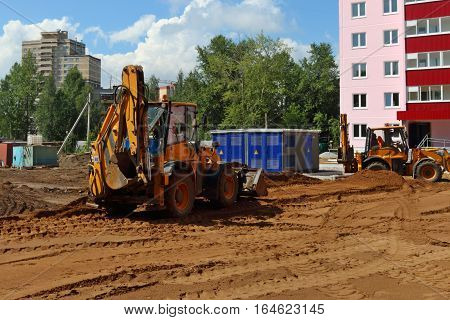 Two yellow tractors work on construction site at summer sunny day