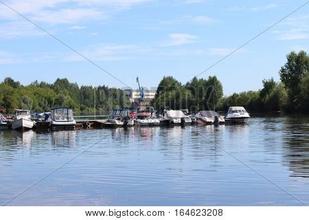 Many small modern motorboats at pier on river at summer sunny day