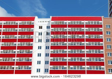 Part of pink residential building with many red loggias at sunny day