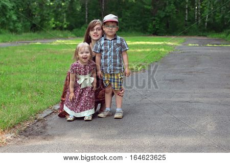 Little pretty girl young mother and boy pose in park at sunny day