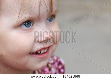 Little pretty blonde girl looks up outdoor closeup shallow dof
