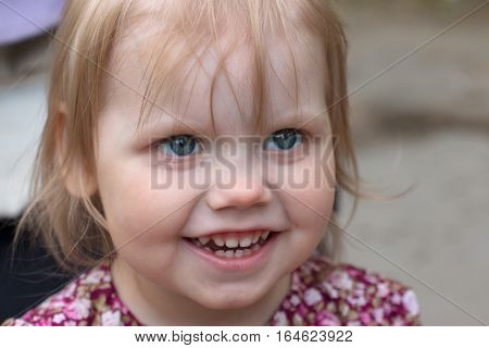 Little smiling blonde girl looks up outdoor closeup shallow dof