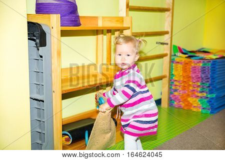 Little child girl playing in kindergarten in Montessori preschool Class. Adorable kid in nursery room.