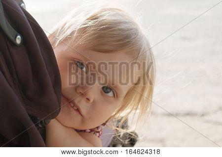 Little smiling blonde girl looks out pram outdoor closeup shallow dof