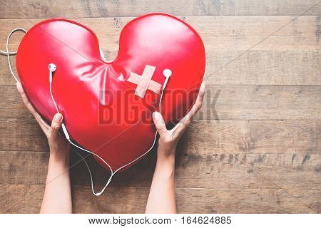 woman hand take care of red broken heart with bandage listening to music on mobile phone Broken heart concept on wood floor