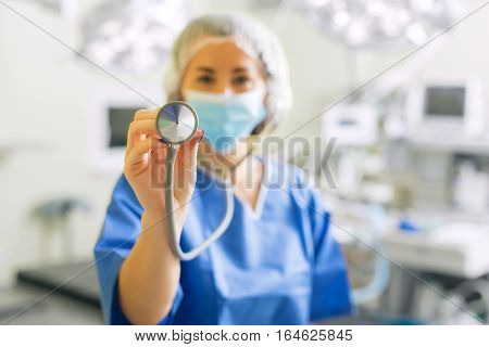 Doctor with stethoscope pointing it out to camera
