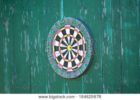Front view of round target for darts hanging on old wooden fence painted green color sid view