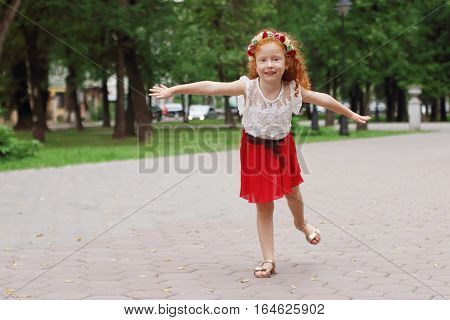 Little smiling girl with red hair depicts bird in green summer park shallow dof