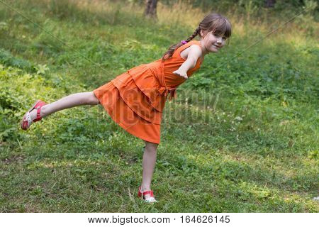 Happy pretty little girl depicts bird on grass in sunny forest and smiles