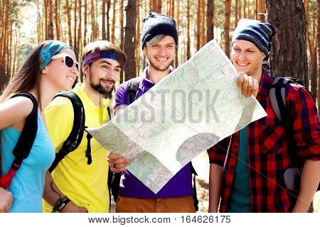 Girl and guys trying to find way with the help of map and compass
