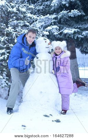 brother and sister making a snowman outdoors in winter