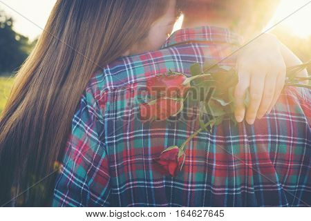 Smiling Woman Hugging Her Boyfriend And Holding The Rose She Got For Valentine's Day.