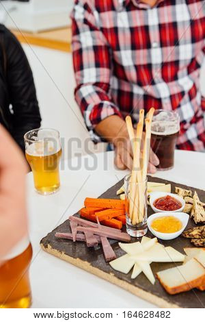 People sitting at table with craft beer and snacks