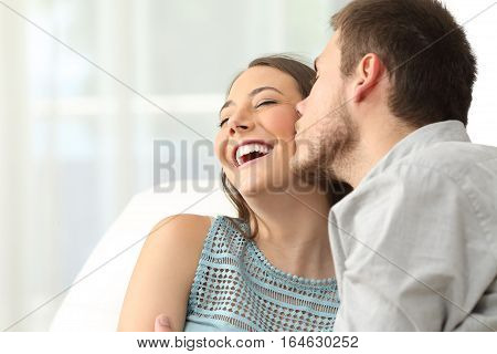 Happy couple. Boyfriend kissing on cheeks to his girlfriend who is laughing