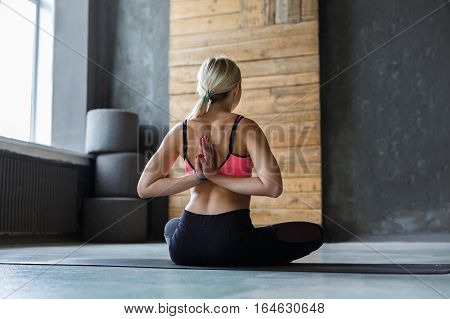 Young slim blond woman in yoga class making asana exercises. Girl do Reverse Prayer Pose, back and shoulders stretching. Healthy lifestyle in fitness club.