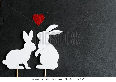 Two white bunnies silhouettes in love on natural black stone background