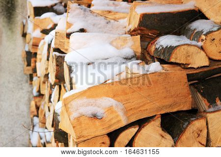 Stacked firewood in winter under the snow. Stock photo