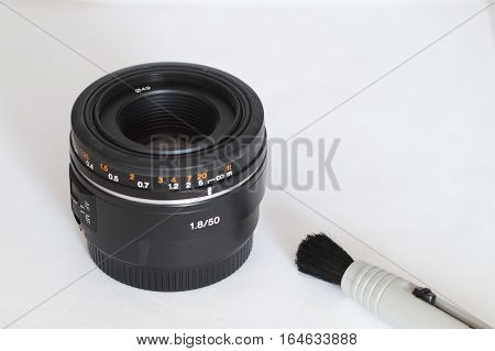 50mm lens for the dslr camera on a white background with cleaning brush