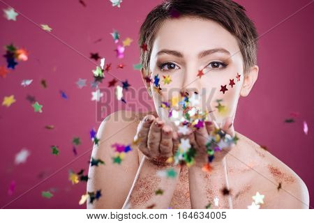 With love. Involved beautiful woman blowing tinsels and looking at you