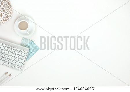 Minimal feminine workspace with keyboard, white and turquoise