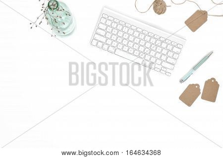 Minimal feminine workspace with keyboard, white and turquoise