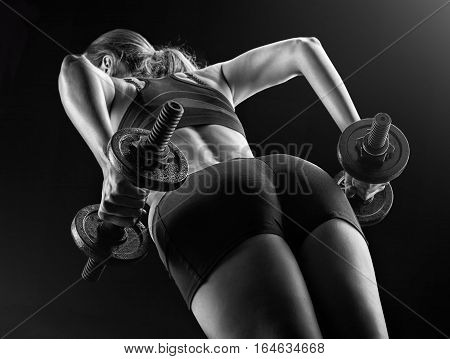 Focus on black shorts. Dark contrast image of fitness woman's back and buttocks. She is training - doing squats with dumbbells on black background in studio.