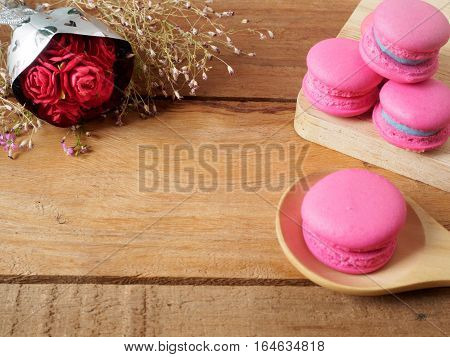 Near roses made of paper have Sweet and pink french macaroons or macarons on spoon and wooden containers. Background of dessert for St Valentine's Day. Selective and soft focus.