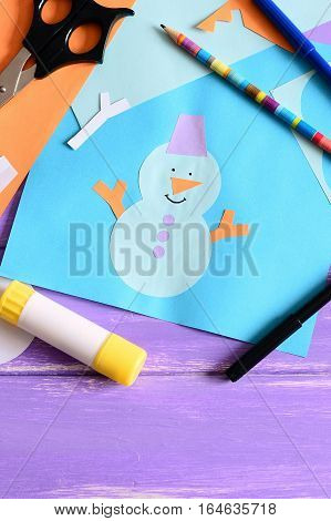 Small kid made a paper card with a snowman, snowflakes and words I love winter. Scissors, glue stick, pencil, markers, colored paper set on a wooden table. Kids paper art background. Closeup