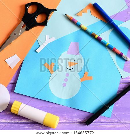 Kid made a paper card with a snowman, snowflakes and words I love winter. Scissors, glue stick, pencil, markers, colored paper sheets on a wooden table. Kids paper crafts. Closeup. Top view