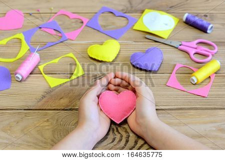 Little girl made a felt heart ornaments. Girl holding a felt heart in his hands. Crafts for Valentine's day or mother's day. Handmade decor. How to create felt valentine ornaments. Easy kids crafts