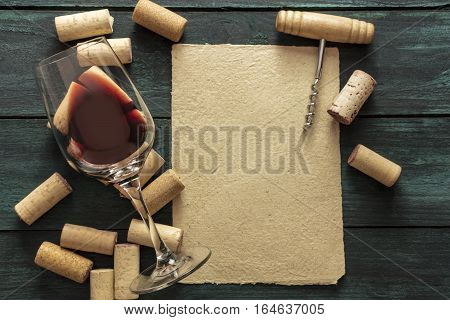A piece of old parchment paper with a frame of corks, a glass of red wine, and a vintage corkscrew on a dark background. A retro-styled wine tasting invitation, horizontal design template