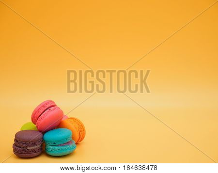Sweet and colourful french macaroons or macarons was placed on gradient orange background. Background of dessert for St Valentine's Day. Selective and soft focus. Vintage Pastel