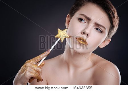 Like a star. Pleasant attrative woman holding lollipop on her chick and posing against black background