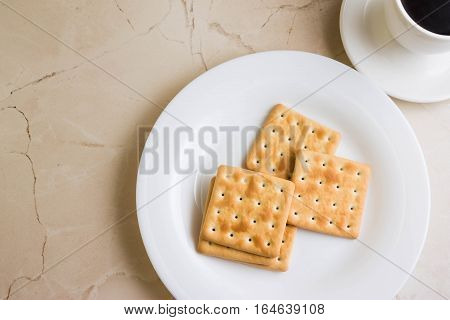 Crackers on a white plate and coffee. Tasty and nutritious breakfast.