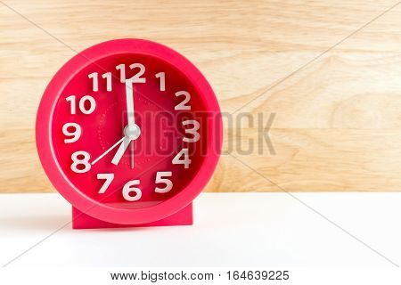 red alarm clock on wood background.can use ad.