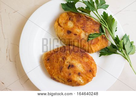 Potato patties with fried onions on a white plate