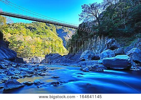 Beautiful flowing river landscape with rocks and drawbridge among the mountains in a sunny day