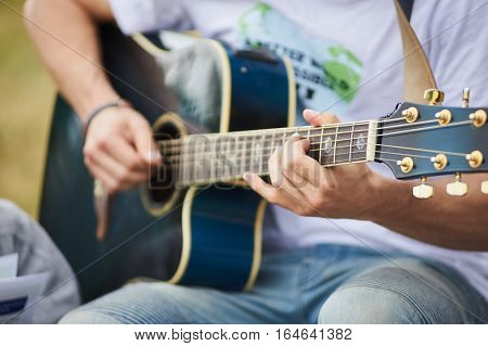 Acoustic Guitarist. Young Man Playing Blue Acoustic Guitar.