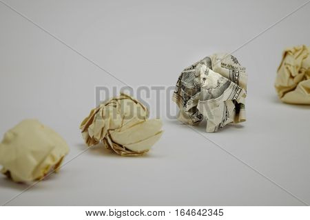 Crumpled dollar bill among office paper. Focus on eyes