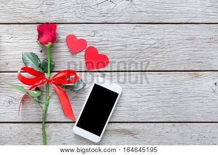 Valentine day internet sales concept, online shopping holiday background with copy space. Mobile phone on rustic wood with rose flower and hearts, top view. Card and advertising mockup