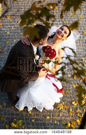Bride Smiles Holding A Fiance's Neck And Standing Under An Autumn Tree